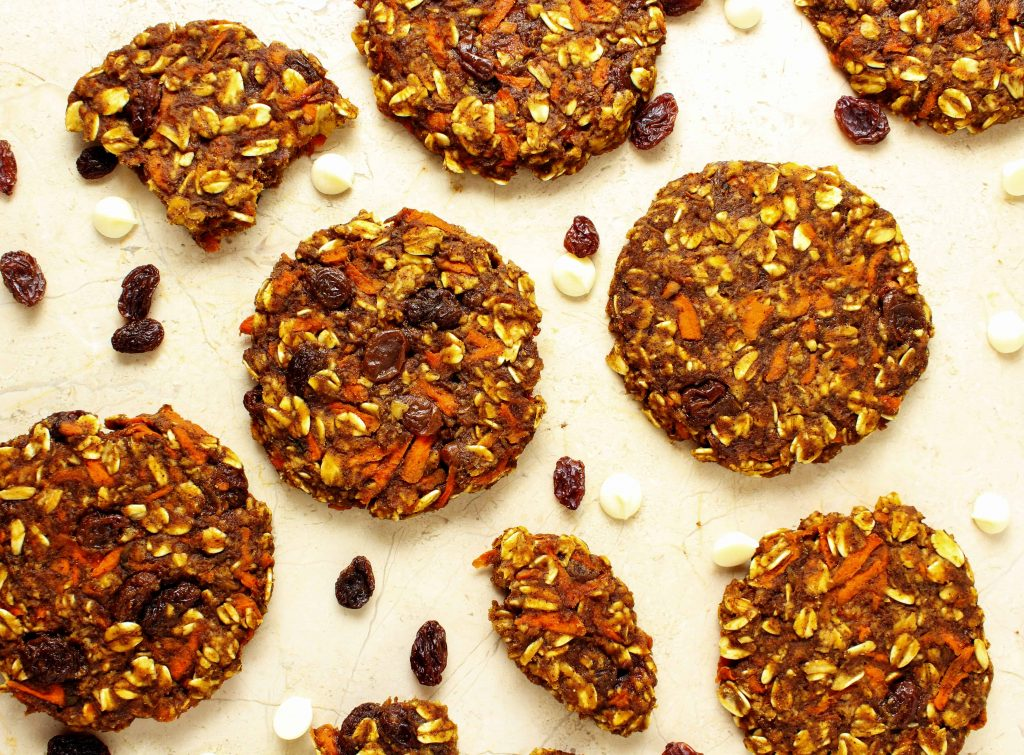 This delicious healthy recipe for carrot cake cookies is so quick and easy you may never make a traditional carrot cake again. These cookies are also high in protein so they make a great post workout or afternoon snack! #postworkout #carrotcake