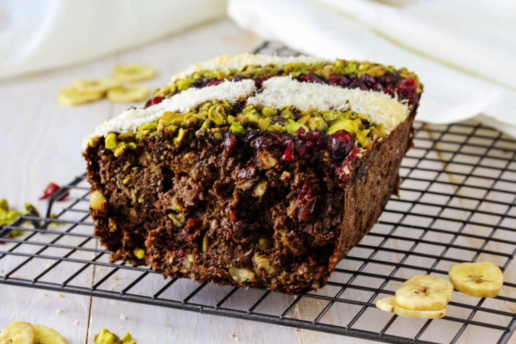 This isn't your grandma's fruit bread! This healthy banana flour fruit bread is the perfect dessert recipe for the holidays! Its moist, soft, the perfect texture to contrast the crunchy and chewy dried fruit and nuts mixed throughout. Use pistachios and cranberries on top for a nice Christmas feel. This loaf is so easy to make, you'll be snacking on it in no time! It's got a delicious banana flavor, a hint of chocolate, and is gluten free and grain free! #HealthyHacks