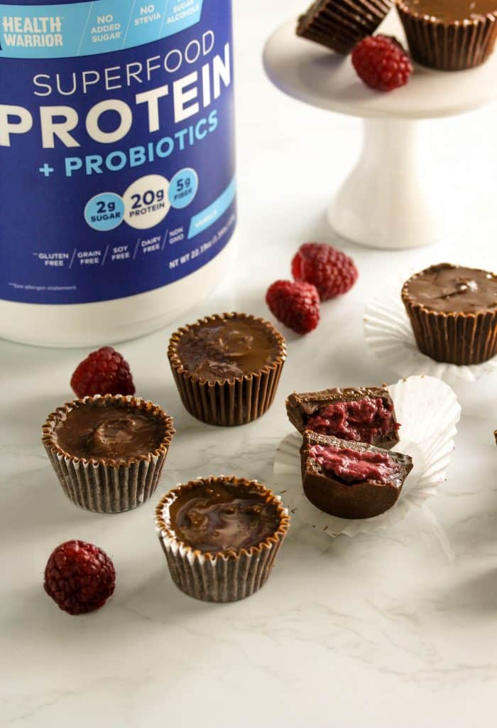 These high protein dark chocolate raspberry cups are the perfect popable healthy snack! They're no bake, easy to make, are low in added sugar and are totally delicious! Pack them up for a sweet afternoon snack or savor them as a late night treat. They're gluten free, vegan, high in protein. #HealthyHacks